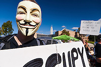 "Ted holds an ""Occupy OC"" sign while wearing a Guy Fawkes mask at the Occupy Orange County, Irvine camp on November 5.  Behind him is the Irvine Civic Center and a woman holding a ""Runaway corp. greed is killing the middle class."" sign."