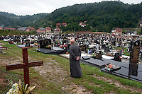 Vojislav Carkic, a priest and Major in the army of Republika Srpska, walks to the graves of Ratko Mladic's mother, father and brother in the village of Donje Miljevici. Former Bosnian Serb general Ratko Mladic is one of the most sought after suspects from the Bosnian conflict. He has been indicted by the UN war crimes tribunal on charges of genocide and crimes against humanity The hill behind Carkic overlooks the city of Sarajevo and marks the Serbian front line during the siege of the city.