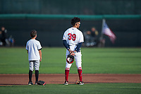 Orem Owlz shortstop Jeremiah Jackson (39) stands next to a young fan during the national anthem before a Pioneer League game against the Ogden Raptors at Home of the OWLZ on August 24, 2018 in Orem, Utah. The Ogden Raptors defeated the Orem Owlz by a score of 13-5. (Zachary Lucy/Four Seam Images)
