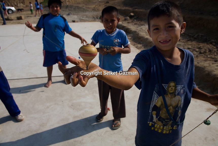 Eight-year-old, Junior, plays with his friends a traditional game of tops in the small community of Cuidad de Dios, located in the highlands of Peru's northern coast. .