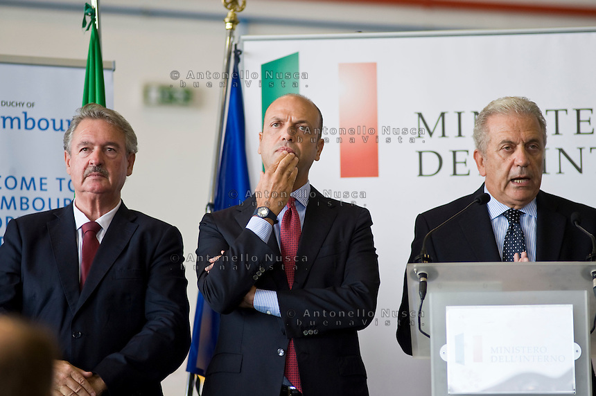 Rome, Italy, October 9, 2015. Italian Interior Minister Angelino Alfano (c), European Commissioner for Migration and Home Affairs Dimitris Avramopoulos, (r), and Luxembourg's Minister of Foreign and European Affairs Jean Asselborn, left, attend a press conference at Rome's Ciampino airport, after the departure of 19 Eritrean refugees to Sweden aboard an Italian Financial police aircraft. The aircraft, carrying 19 Eritreans, will bring the first refugees to Sweden under the European Union's new resettlement program aimed at redistributing asylum-seekers from hard-hit receiving countries.