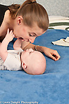 5 month old baby boy on  back closeup face to face with mother who is talking with exaggerated expression