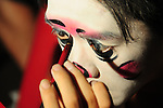 Ghost Month, Kaohsiung - Performer of the Rom Shing Hakka Opera Troupe putting on make-up before an open-air stage performance during Ghost Month in front of the Bao-Jhong Yi-Min Temple in Kaohsiung, Taiwan.