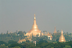 Swedagon Pagoda dominates the city skyline, according to tradition it is 2,500 years old; the oldest pagoda in the world. Souvenirs for the mainly local pilgrims clutter one of the many entrances to the pagoda.  Shwedagon Paya Rangoon  Myanmar Burma 2006.