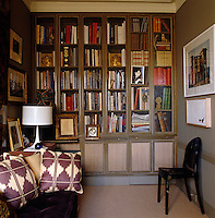 An entire wall of the study is filled with built-in bookshelves with fabric-lined cupboard space underneath