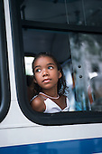 Rio de Janeiro, Brazil. Girl looking out of the window of a bus.