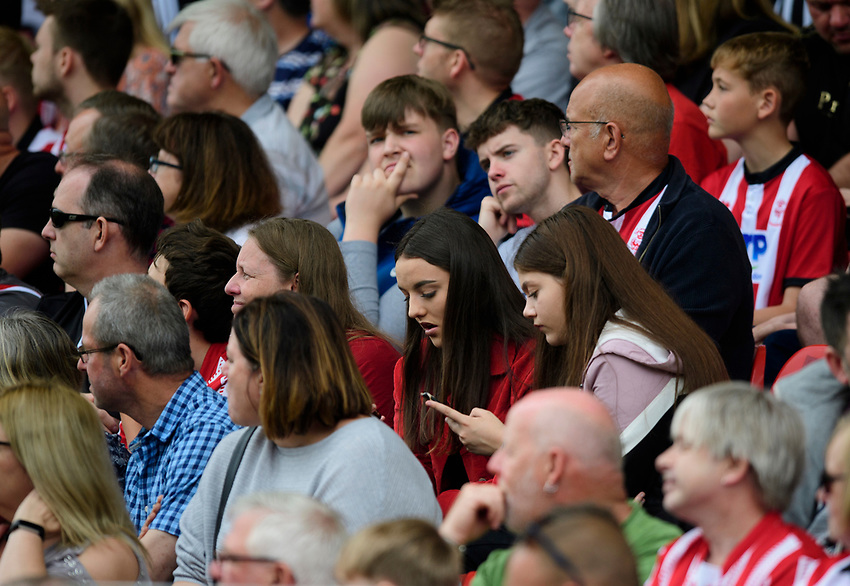 Lincoln City fans watch their team in action<br /> <br /> Photographer Chris Vaughan/CameraSport<br /> <br /> Football Pre-Season Friendly - Lincoln City v Sheffield Wednesday - Saturday July 13th 2019 - Sincil Bank - Lincoln<br /> <br /> World Copyright © 2019 CameraSport. All rights reserved. 43 Linden Ave. Countesthorpe. Leicester. England. LE8 5PG - Tel: +44 (0) 116 277 4147 - admin@camerasport.com - www.camerasport.com