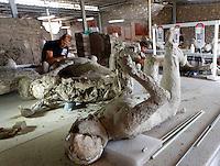 Restauratori al lavoro in un laboratorio negli scavi archeologici di Pompei per  un progetto di analisi restauro e conservazione che coinvolge 86 calchi di vittime dell'eruzione del vesuvio nel  del 79ac<br /> <br /> A restorer works on pietrified victim of eruption of Vesuvius in 79 BC in Pompeii in the laboratory  of excavation site . the project includes the study, preservation and restaration of 86 cast