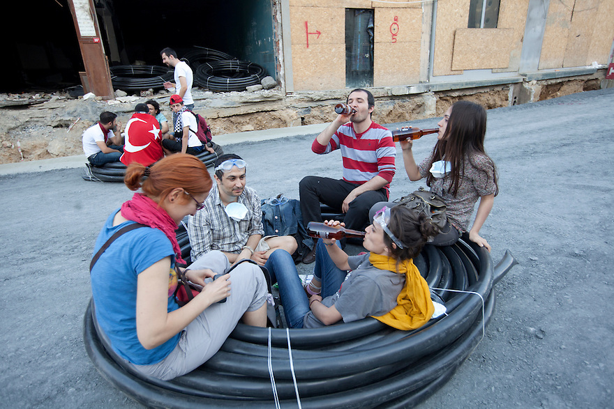 ISTANBUL, TURKEY-- Protesters celebrate with a beer while sitting inside tubing located on the construction site for one of the Turkish government's controversial projects on Saturday, June 1, 2013.  Protesters and police have clashed over recent days regarding the future of Gezi Park, which is slated to become a shopping mall. PHOTO BY JODI HILTON