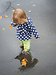 Toddler playing on wet asphalt with fall leaves and reflection.