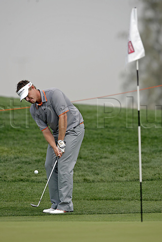 5 March 2005: Swedish golfer Joakim Haeggman (SWE) chips onto the 1st green during round three of the Dubai Desert Classic held on the Majlis Course at the Emirates Golf Club, Dubai, United Arab Emirates. Photo: Neil Tingle/Action Plus..050305 male man men golf golfer golfers chip pitch chipping pitching