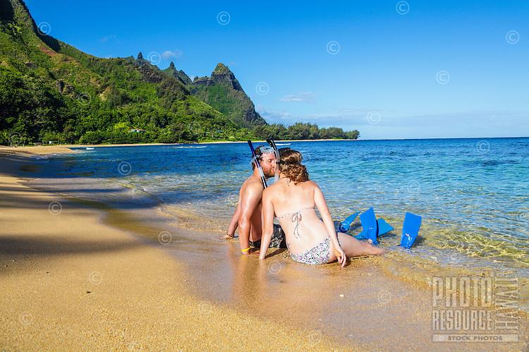 Honeymooners in snorkeling gear kiss at Tunnels Beach on Kaua'i.