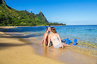 Honeymooners in snorkeling gear kiss at Tunnels Beach on Kaua'i.