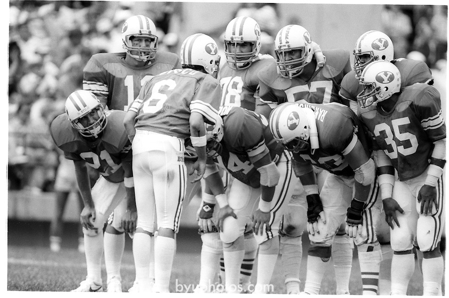 FTB 703 M 42<br /> <br /> BYU vs Tulsa. Quarterback 6 Robbie Bosco talks to offensive players: 21 Kelly Smith. 78 Dave Wright. 57 Robert Anae. 63 Randy Rawlinson. 35 Lakei Heimuli.<br /> <br /> September 15, 1984<br /> <br /> Photo by Mark Philbrick/BYU<br /> <br /> &copy; BYU PHOTO 2009<br /> All Rights Reserved<br /> photo@byu.edu  (801)422-7322