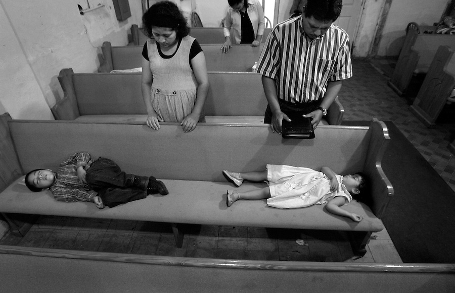 Octavio Cruz and his wife Isabel Cruz pray while their children Octavio, 5, and Karina, 2, nap during a church service in Warsaw, NC.
