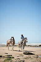 A man on a horse with another on a bridle behind on a beach.