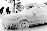 Switzerland. Canton Geneva. Versoix. Frozen car. The car has been parked close to the lake. The wind blew lake's water on the car which froze and is totaly stuck in the ice. Tourists take pictures. Versoix is distant 10 km from Geneva. 12.02.2012 © 2012 Didier Ruef