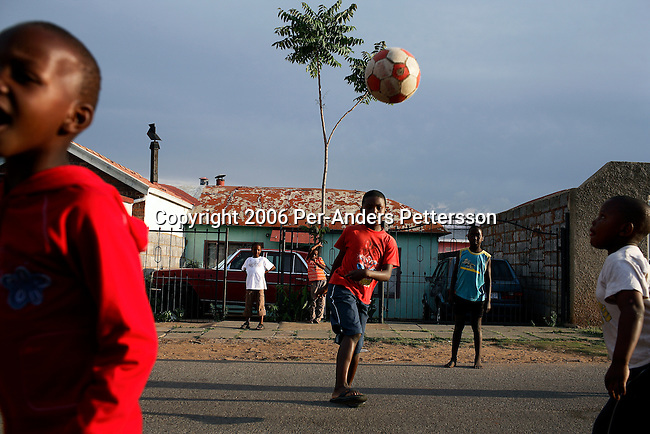 SOWETO, SOUTH AFRICA OCTOBER 29: Boys play soccer in the street as the sun goes down October 29, 2006 in the Orlando West section of Soweto, Johannesburg, South Africa. Soweto is South Africa&rsquo;s largest township and it was founded about one hundred years to make housing available for black people south west of downtown Johannesburg. The estimated population is between 2-3 million. Many key events during the Apartheid struggle unfolded here, and the most known is the student uprisings in June 1976, where thousands of students took to the streets to protest after being forced to study the Afrikaans language at school. Soweto today is a mix of old housing and newly constructed townhouses. A new hungry black middle-class is growing steadily. Many residents work in Johannesburg but the last years many shopping malls have been built, and people are starting to spend their money in Soweto.  <br /> (Photo by Per-Anders Pettersson)