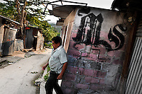 A Salvadoran man passes in front of the Mara Salvatrucha graffiti, a symbol marking the gang's territory in a gang neighborhood in San Salvador, El Salvador, 19 May 2011. Although the murder rate in the country has dropped significantly, after a truce between two major street gangs (Mara Salvatrucha and Barrio 18) was agreed in 2012, the lack of security and violence are still the main issues in people's daily life. Due to the fact the gangs have never stopped their criminal activities (extortions, distribution of drugs and kidnappings), the Police anti-gang forces keep running their operations and chasing the 'homeboys' (how the gang's foot soldiers usually call themselves) in the poor, socially deprived suburbs of Salvadoran cities.