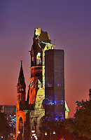 Berlin, Germany.  Kaiser-Wilhelm-Gedachtniskirche. The ruins of one of the city?s churches left as a reminder  of the results of war.  An octagonal spire by architect Egon Eiermann stands next to the ruin. Evening..