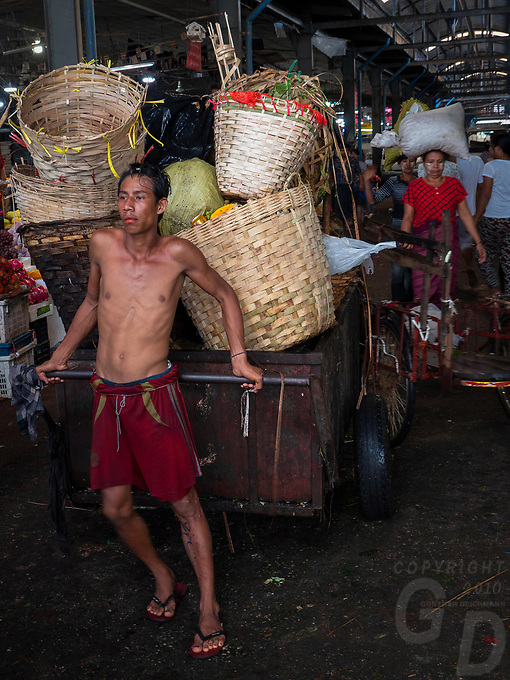 Pulling a large cart and Life at the whole sale vegetable Market in Yangon, Myanmar, Burma