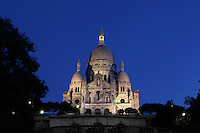 A low angle view of the Sacre-Coeur Basilica, 1884-1914, Paul Abadie, Paris, France at dawn, Built in white travertine on the top of the Butte de Montmartre, the Romano-Byzantine style Sacré-Coeur was designed as a monument to those who died in the Paris Commune during the Franco-Prussian War, 1870-71. Picture by Manuel Cohen