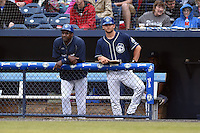 Asheville Tourists hitting coach Mike Devereaux (12) and manager Warren Schaeffer (13) during game one of a double header against the Greenville Drive on April 18, 2015 in Asheville, North Carolina. The Tourists defeated the Drive 2-1. (Tony Farlow/Four Seam Images)