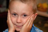 Impish Polish boy age 6 holding his head between his hands. Zawady Central Poland
