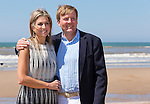King Willem-Alexander of the Netherlands (L) and his wife Queen Maxima (R) pose for photographers during a photo session on the beach near Wassenaar, the Netherlands, July 10, 2015. © Michael Kooren