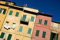 Colourful houses with green shutters, bathed in afternoon sunlight, Siena, Italy