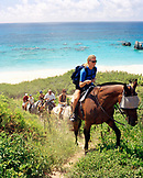 BERMUDA, Horseshoe Bay, tourists enjoying horseback riding with sea in the background