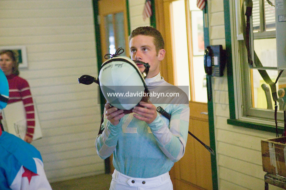 French jockey Julien Leparoux (R) looks up at a race replay on a TV screen before a race in Saratoga Springs, NY, United States, 4 August 2006.<br />