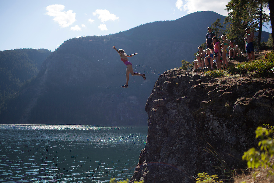A cliff jumper leaps in front of a group at Ross Lake, WA, USA