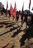 Lolgorian, Kenya. Siria Maasai; Eunoto ceremony; line of moran running through the Manyatta carrying flags.