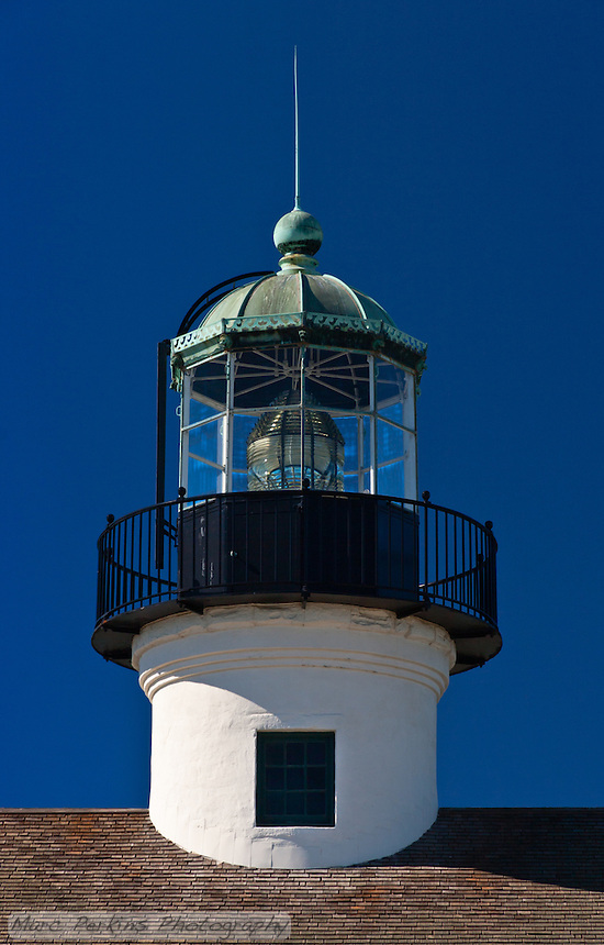 A head-on look at the lantern room and lens of Old Point Loma Light, seen from the east.  The window visible in the lantern tower is the one visitor's can look out when they climb the lighthouse stairs.  The lighthouse's green (copper) roof is clearly visible, with its beautiful cut-out wave edging visible.  The shingle roof of the lighthouse's main building is visible at the bottom of the picture.  The lighthouse is in Cabrillo National Monument near San Diego, CA.