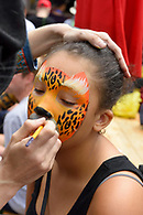 A girl getting her face painted like a leopard.