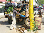 Dominican man cleans up trash on a busy street in Las Terranas, Samana, Dominican Republic