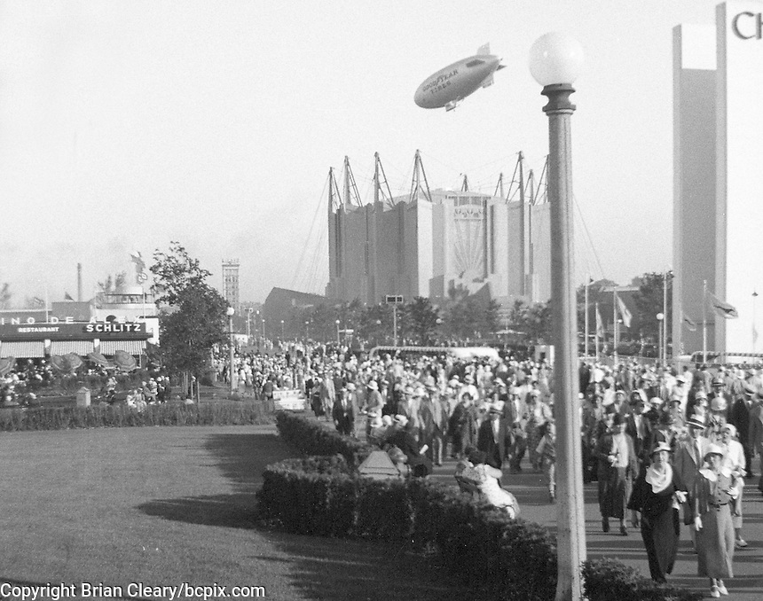 "A crowd of fairgoers walks down a sidewalk in front of the Travel and Transport building at the 1933 Chicago ""Century of Progress""  World's Fair as the GoodYear blimp flies overhead.  (Photo by bcpix.com)"