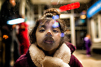 A Bangladeshi child Tazree kisses a glass playfully, as she looks the street from the inside of a money booth room in New York City, United States.