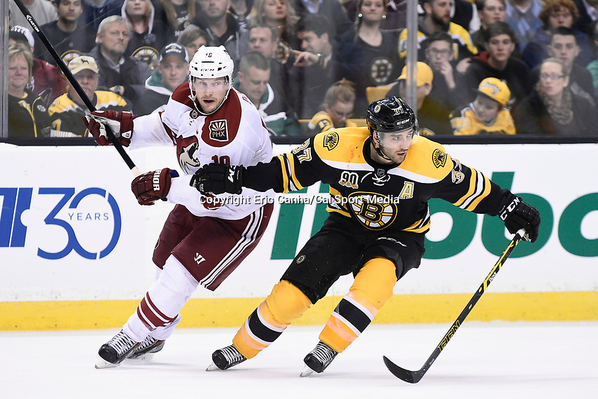 March 13, 2014 - Boston, Massachusetts , U.S. - Phoenix Coyotes right wing Shane Doan (19) and Boston Bruins center Patrice Bergeron (37) in game action during the NHL game between the Phoenix Coyotes and the Boston Bruins held at TD Garden in Boston Massachusetts. The Bruins defeated the Coyotes 2-1 in regulation time. Eric Canha/CSM