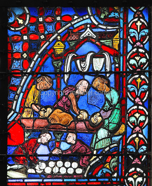 Three men in a bakery work the dough into balls to be baked in the oven by the 2 men below. Donor window of the bakers, from the Apostles window, 1212-25, in the axial chapel in the ambulatory of Chartres Cathedral, Eure-et-Loir, France. This window represents the birth of the Church, as the apostles are the first pillar of the church and therefore has the site with the most sunlight to illuminate the colours. Chartres cathedral was built 1194-1250 and is a fine example of Gothic architecture. Most of its windows date from 1205-40 although a few earlier 12th century examples are also intact. It was declared a UNESCO World Heritage Site in 1979. Picture by Manuel Cohen
