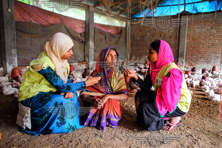 Poultry farmer Resma Begum, who was supported in her enterprise by NGO Dwip Unnayan Songstha (DUS), talks with a reporters from radio Sagor Dwip.