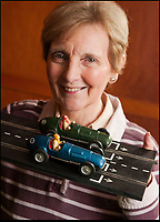 BNPS.co.uk (01202 558833)<br /> Pic: PhilYeomans/BNPS<br /> <br /> Diane Francis(72) the widow of founder Freddie, with an original set from 1957.<br /> <br /> These fascinating photos tell the story of 60 years of Scalextric which grew from humble beginnings into a British institution. <br /> <br /> When enterprising Freddie Francis launched the car racing toy in 1957 at his factory in Havant, Hants, he could never have known they would still be a household name 60 years later.<br /> <br /> Today, Scalextric are produced by English toy maker Hornby Hobbies and demand for the much-loved slot cars is still as strong as ever.
