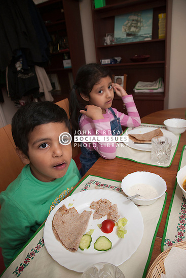 Asian children at dining room table.