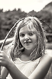 CANADA, Vancouver, British Columbia, a young girl holding a stick at Port Graves, Gambier Island, Howe Sound, B&W