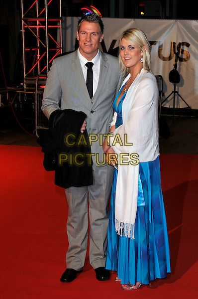 "JEAN DE VILLIERS & GUEST .Attending the ""Invictus'"" UK Film Premiere at the Odeon West End cinema, Leicester Square, London, England, January 31st, 2010..arrivals full length grey gray suit black tie blue long maxi dress print white pashmina wrap shawl .CAP/PL.©Phil Loftus/Capital Pictures"