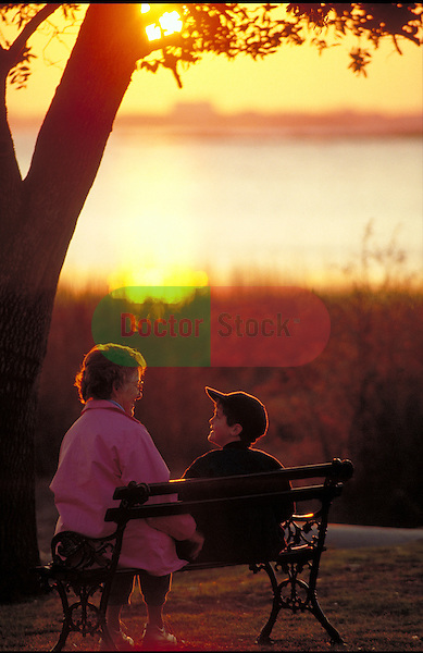 grandmother talking with grandson on park bench
