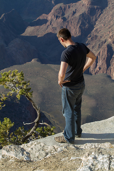 Man peers over the edge in Grand Canyon National Park, Arizona. . John offers private photo tours in Grand Canyon National Park and throughout Arizona, Utah and Colorado. Year-round.