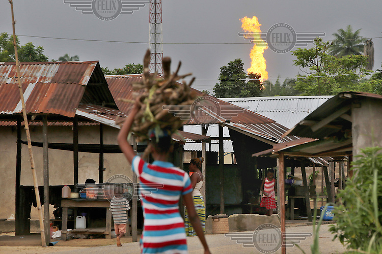 A girl carries firewood along a street while the Oshie gas flare, belonging to Agip oil company, burns in the background in the Akaraolu community. <br /> The Rumuekpe community suffered much damage during the conflict among various rival militants and cult gangs over access to oil money. The inter-communal violence killed many people, including women and children, between 2005-08. Thousands more were displaced by fighting that left homes, schools and churches in ruins with many suffering poverty and homelessness.