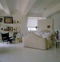 The bed is located in the centre of the room against a floating wall with a double row of black and white photographs displayed on ledges